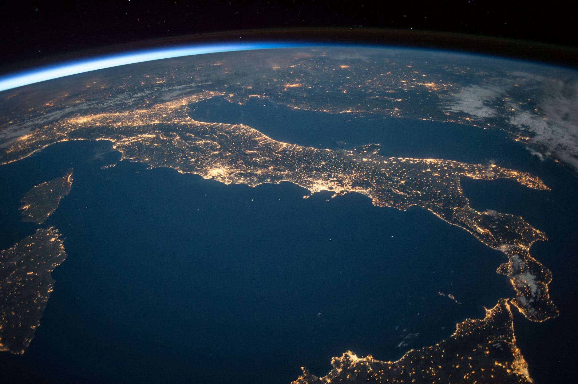 An image of Italy from space at night. You can see city lights.