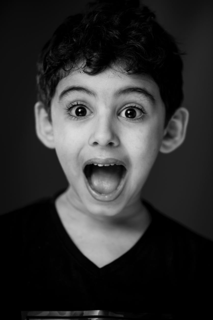 a boy has an excited expression on his face with eyes and mouth wide open